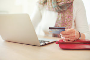 Senior woman's hand holding a credit card while in front of the laptop shopping online